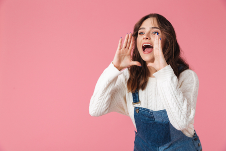 Portrait of a pretty young girl shouting loud isolated over pink background Stock Photo