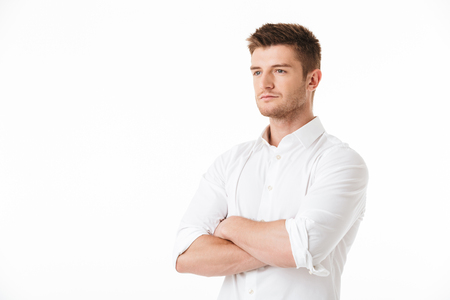 Portrait of a confident young man standing with arms folded isolated over white background