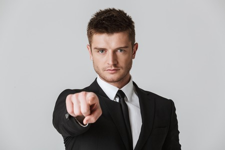 Portrait of a confident young businessman in suit pointing finger at camera isolated over gray background Stock Photo
