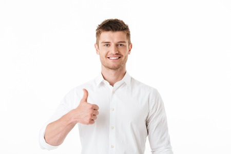 Portrait of a smiling young man looking at camera and showing thumbs up isolated over white background