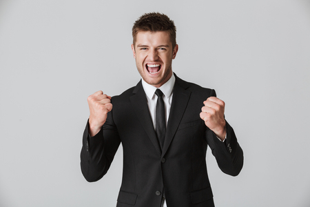 Portrait of an angry young businessman in suit showing his fists and screaming isolated over gray background