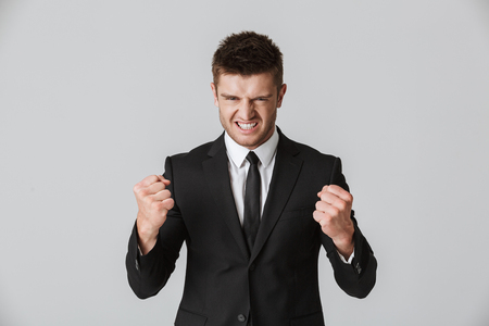Portrait of an angry young businessman in suit showing his fists isolated over gray background
