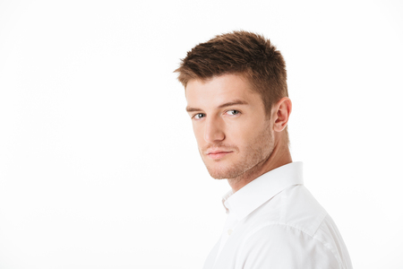 Portrait of a charming young man looking at camera isolated over white background 스톡 콘텐츠