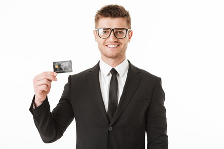 Portrait of a happy young businessman in suit and eyewear showing plastic credit card isolated over white background Stock Photo - 104564990