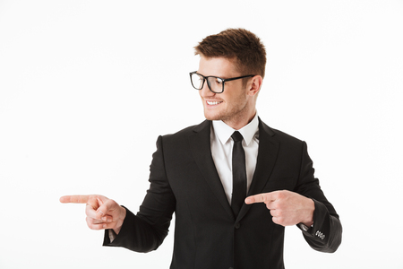 Portrait of a happy young businessman in suit and eyewear pointing fingers away at copy space isolated over white background