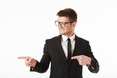 Retrato de un joven empresario feliz en traje y gafas apuntando con el dedo hacia el espacio de copia aislado sobre fondo blanco.