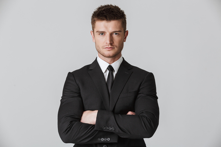 Close up portrait of a confident young businessman in suit looking at camera isolated over gray background Reklamní fotografie