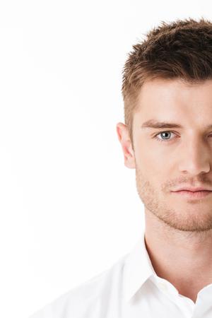 Image recadrée du visage d'un jeune homme sérieux regardant la caméra isolée sur fond blanc