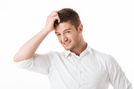 Portrait of a confused young man scratching his head isolated over white background