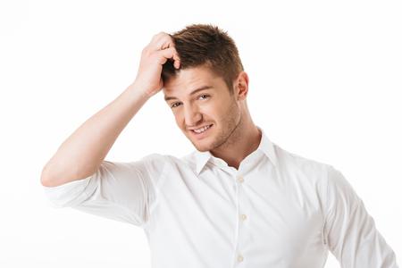 Porträt eines verwirrten jungen Mannes, der seinen Kopf isoliert über weißem Hintergrund kratzt Standard-Bild