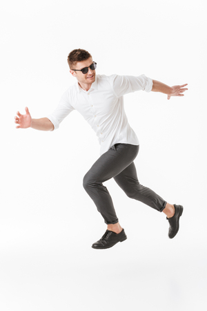 Full length portrait of a confident young man in sunglasses running away isolated over white background