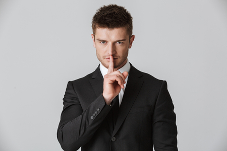 Portrait of a confident young businessman in suit showing silence gesture isolated over gray background Foto de archivo