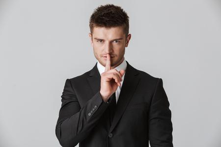 Retrato de un joven empresario confiado en traje mostrando gesto de silencio aislado sobre fondo gris