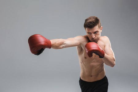 Portrait of a motivated shirtless sportsman wearing boxing gloves isolated over gray background