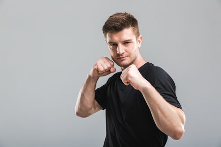 Portrait of a focused young sportsman standing ready to fight isolated over gray background Stock Photo