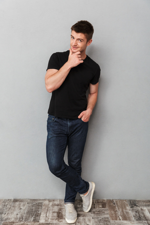 Full length portrait of a charming young man looking at camera over gray background