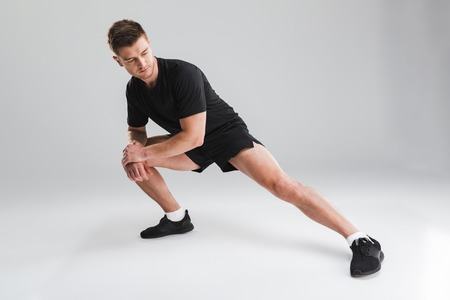 Portrait of a fit young sportsman doing stretching exercises isolated over gray background