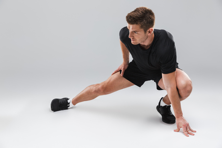 Portrait of a motivated young sportsman doing stretching exercises isolated over gray background