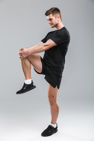 Portrait of a focused young sportsman doing stretching exercises isolated over gray background