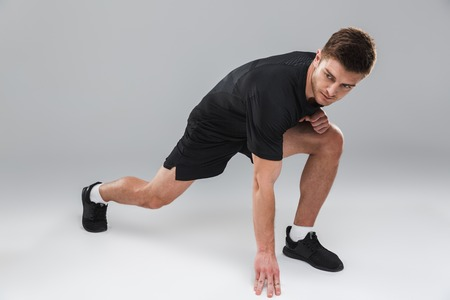 Portrait of a concentrated young sportsman doing stretching exercises isolated over gray background