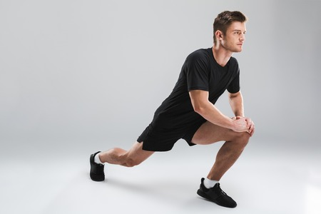 Portrait of a confident young sportsman doing stretching exercises isolated over gray background
