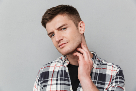 Portrait of a concerned young man in plaid shirt touching his face over gray background