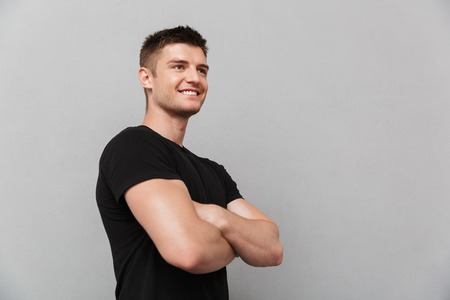 Portrait of a confident young man standing with arms folded isolated over gray background
