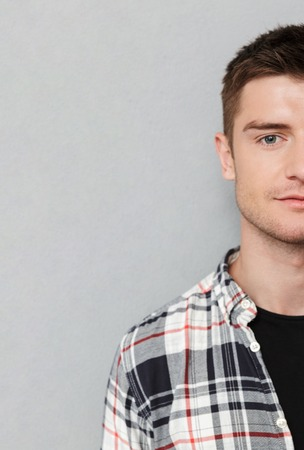 Half portrait of a serious man in plaid short looking at camera over gray background
