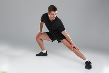 Portrait of a healthy young sportsman doing stretching exercises isolated over gray background