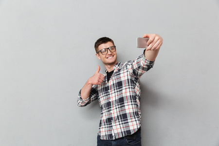 Portrait of a smiling young man in plaid shirt taking a selfie over gray background
