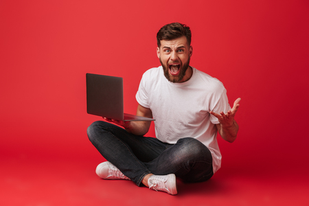 Photo of displeased bored man in t-shirt and jeans screaming and gesturing in irritation while sitting on floor with laptop isolated over red background