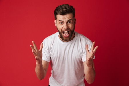 Image of angry emotional young man standing isolated over red wall background. Looking camera.