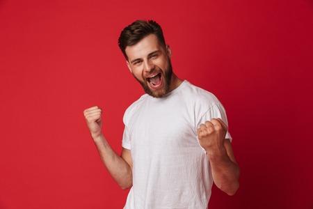 Foto van opgewonden jonge knappe man permanent geïsoleerd over rode muur achtergrond maken winnaar gebaar.