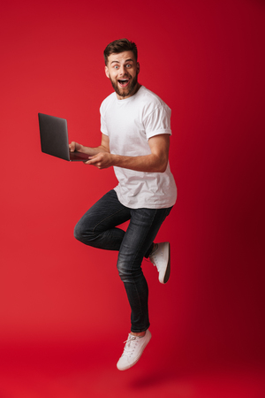 Image of surprised young man jumping isolated over red wall background using laptop computer. Looking camera. Stockfoto