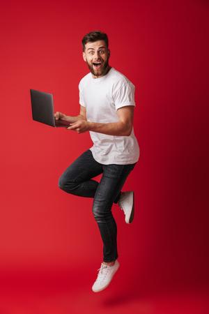 Imagen de un joven sorprendido saltando aislado sobre fondo de pared roja usando una computadora portátil. Mirando la cámara. Foto de archivo