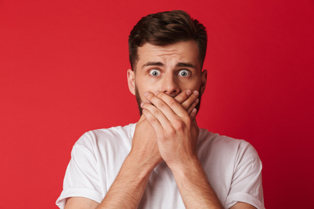 Image of scared young man covering mouth with hands standing isolated over red wall background.