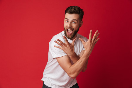 Picture of excited screaming young handsome man standing isolated over red wall background. Looking camera.