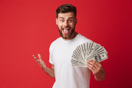 Image of excited screaming young man isolated over red wall background holding money.
