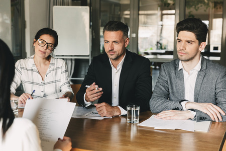 Business, career and placement concept - three executive directors or head managers sitting at table in office and interviewing woman for job in company