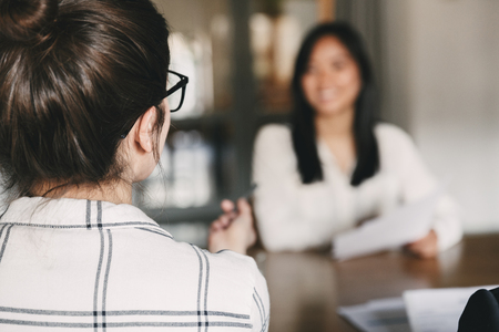 Business, career and placement concept -photo from back of businesswoman interviewing and talking with new female worker during corporate meeting