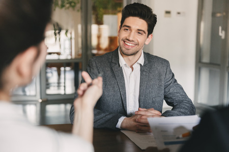 Business, career and placement concept - smiling caucasian man 30s negotiating with committee of businesslike people during job interview in office