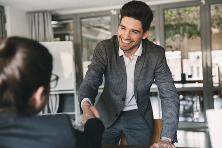 Business, career and placement concept - joyful young man 30s smiling and shaking hands with businesswoman when was recruited during interview in office Stock Photo