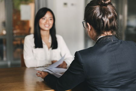 Business, career and placement concept -photo from back of businesswoman interviewing and talking with female applicant during job interview Stock Photo