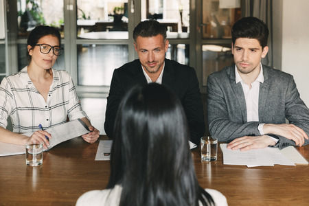 Business, career and recruitment concept - group of employers in formal wear sitting at table in office and interviewing woman for job in big corporation