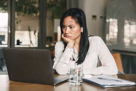 Photo of perplexed asian woman 20s wearing white shirt and earphones frowning and looking on laptop with puzzlement while sitting at table in office
