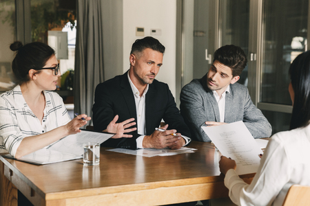 Business, career and placement concept - three executive directors or head managers sitting at table in office and discussing work with new personnel during interview