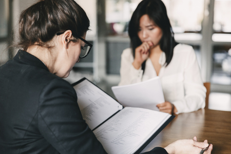 Photo from back of businesswoman interviewing and talking with nervous female applicant during job interview - business, career and placement concept