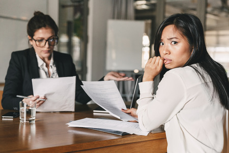 Photo of stressed asian woman expressing panic while sitting at table in office and talking to female employee during job interview - business, career and recruitment concept