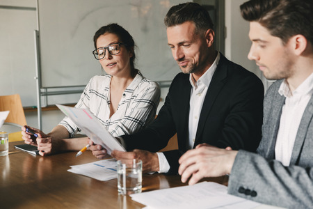 Group of business people in formal suits sitting at table in office and examining resume of new personnel during job interview - business, career and placement concept