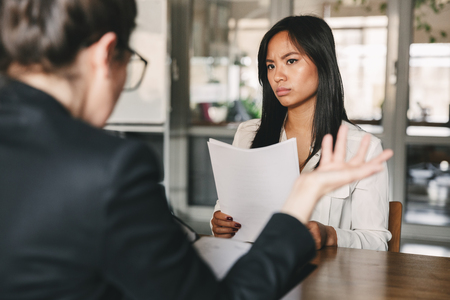 Image of serious asian woman looking and talking to businesswoman while sitting at table in office during job interview - business, career and recruitment concept